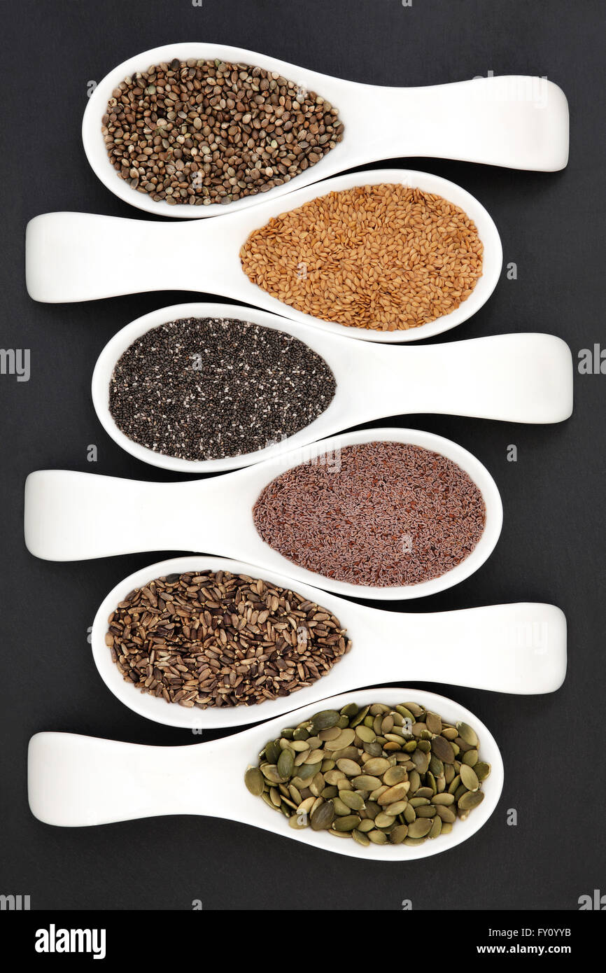 Healthy seed food selection in white porcelain scoops over grey slate background. - Stock Image