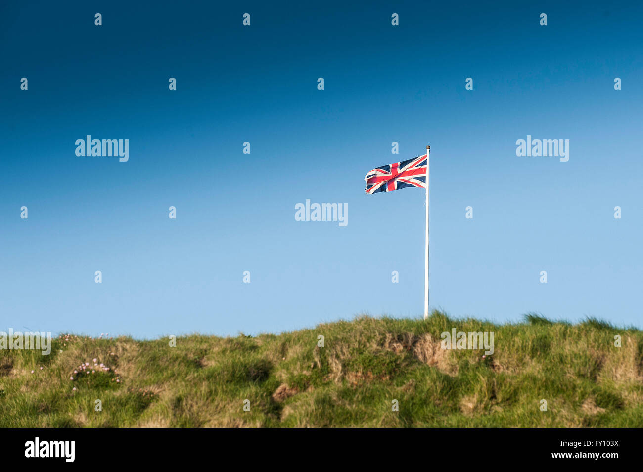 A Union Flag flying from a flagpole. - Stock Image