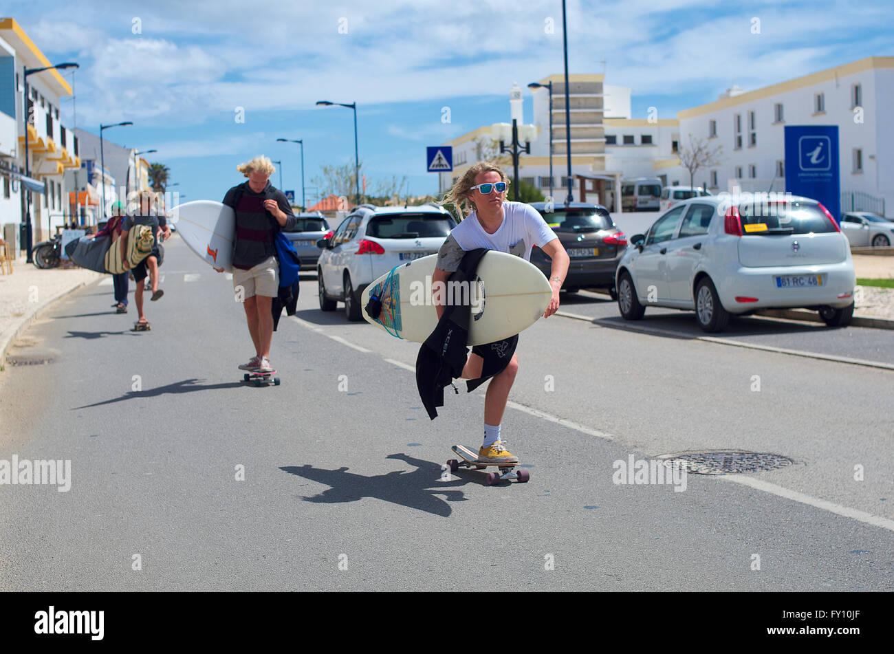 Blonde surfers skateboarding down the road, Sagres Portugal - Stock Image