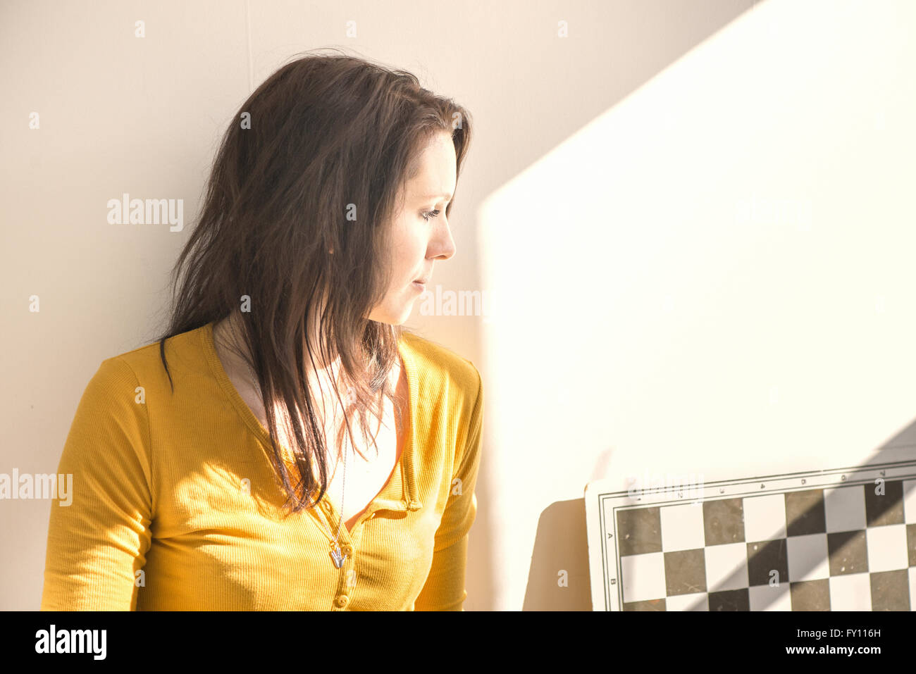Serious woman and chessboard in home interior. Concept of strategy, leisure activity and contemplation. - Stock Image