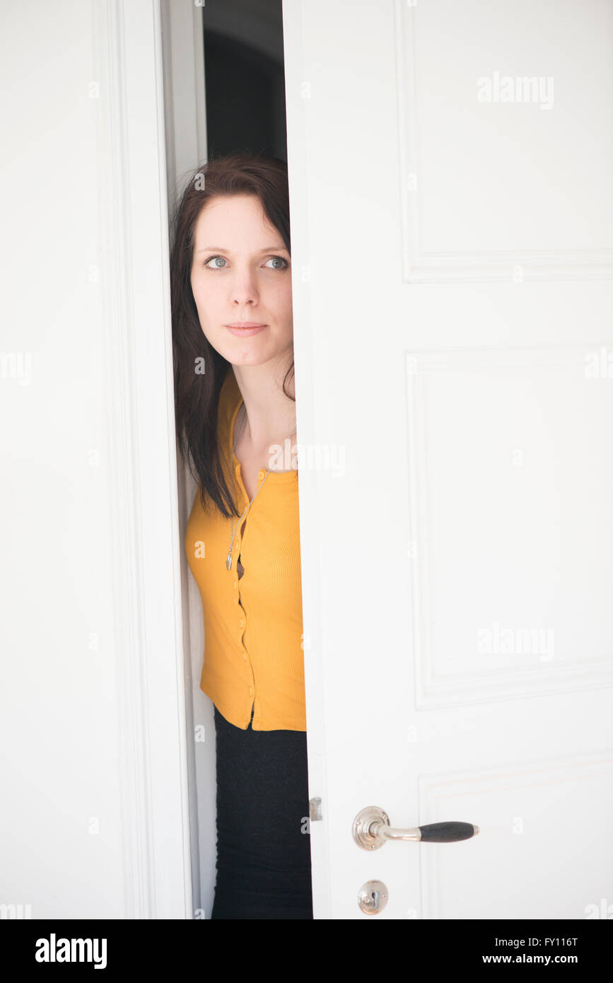Serious woman opening door and looking. Concept of curiosity, suspicion and anxiety. - Stock Image