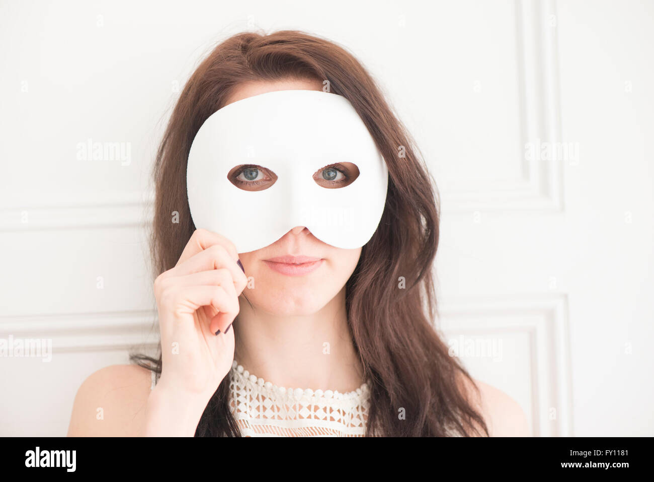 Woman hiding face behind white mask. Concept of identity, mystery, and disguise. - Stock Image
