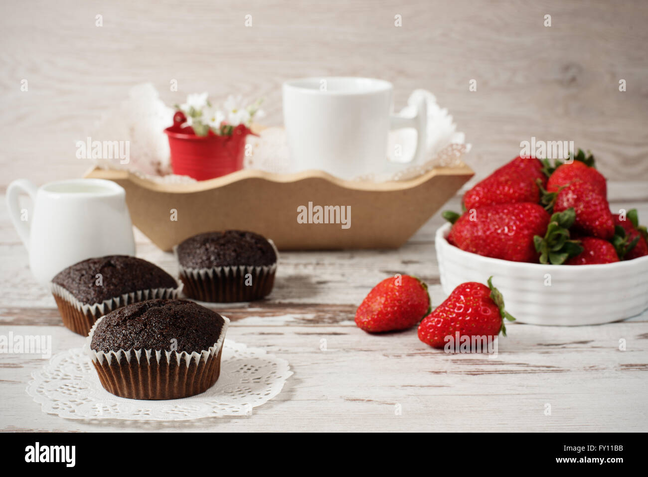Chocolate muffins, coffee, strawberries, a vase of white flowers. Light wood rustic background - Stock Image