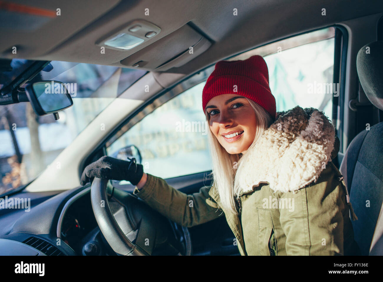 Portrait of happy woman in warm clothing driving car - Stock Image