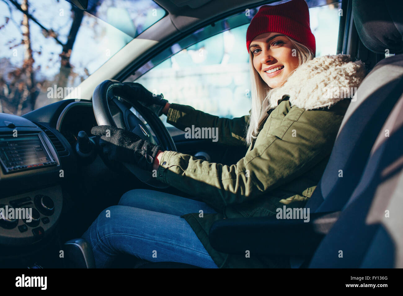 Portrait of happy young woman in warm clothing driving car - Stock Image