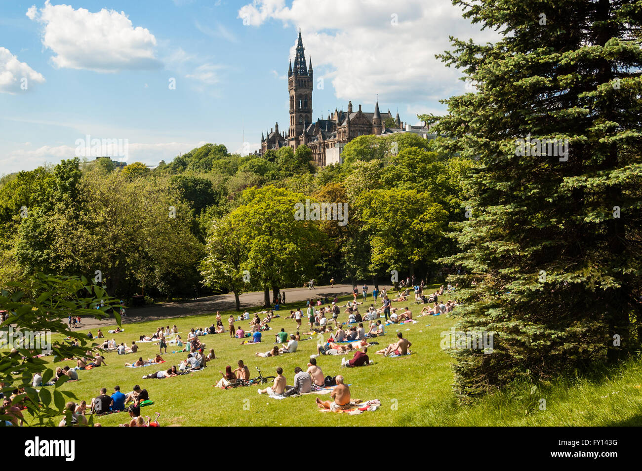 View of Kelvingrove Park full of people enjoying the Scottish summer with main building of Glasgow University on - Stock Image