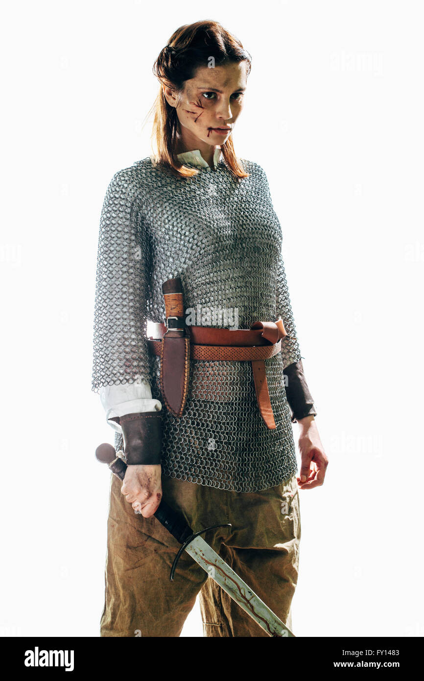 Injured woman wearing chain mail holding sword against white background - Stock Image