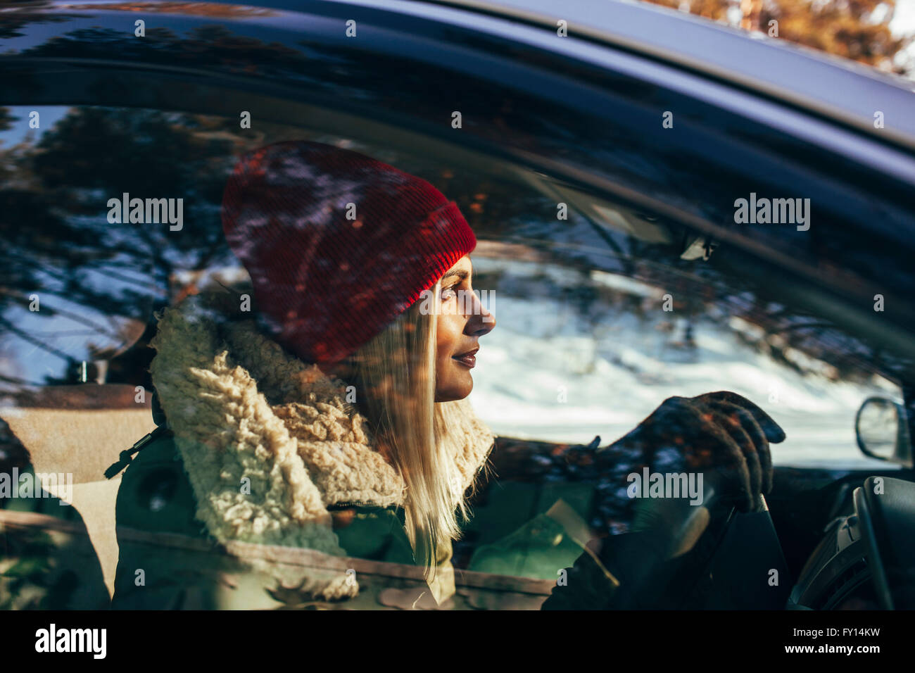 Woman in warm clothing driving car - Stock Image