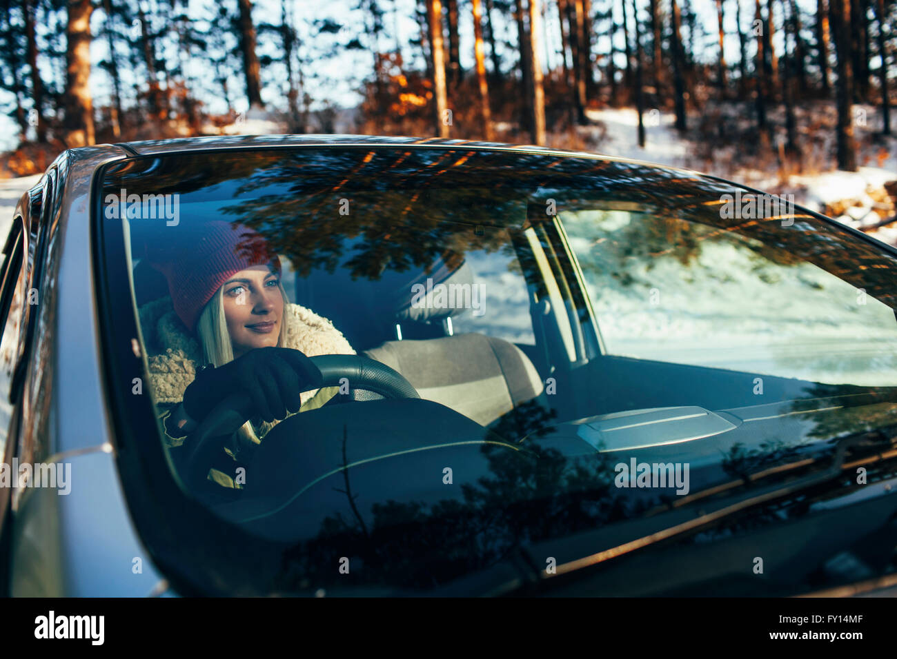 Beautiful woman in warm clothing driving car - Stock Image