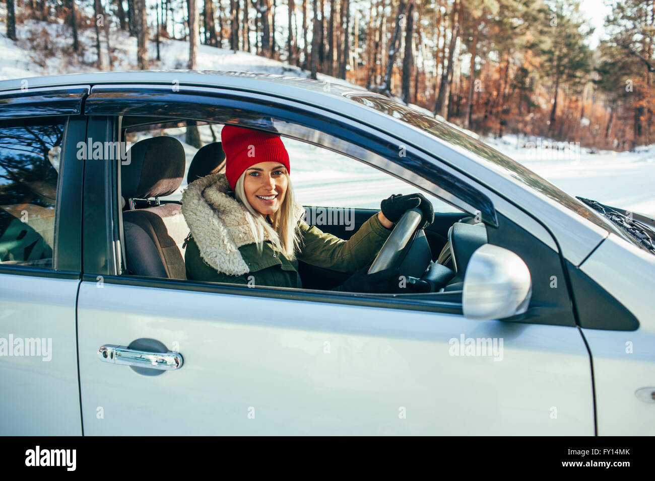 Portrait of smiling woman in warm clothing driving car - Stock Image