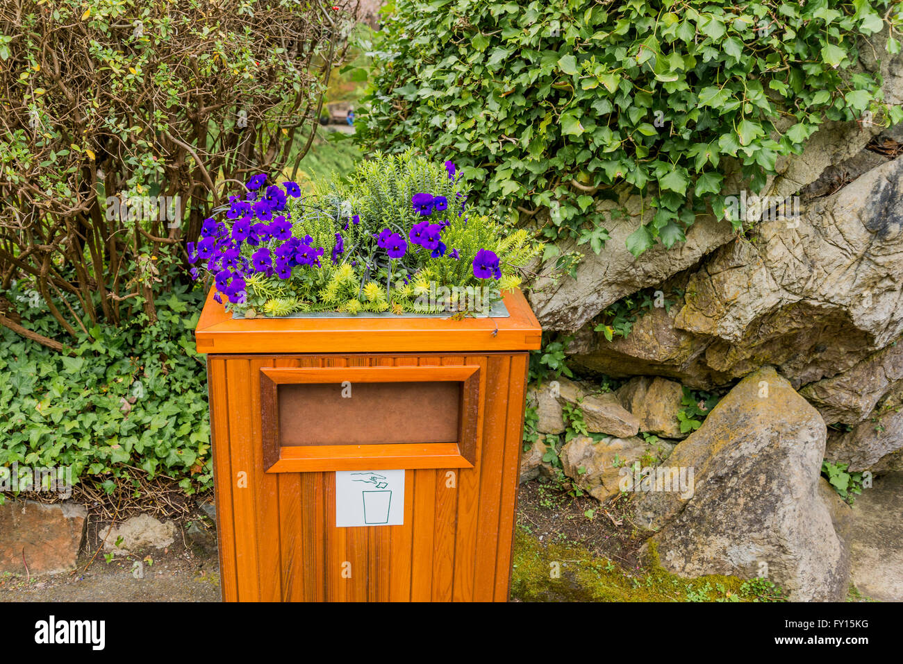Litter bin with flower arrangement, Butchart Gardens, Brentwood Bay, near Victoria, British Columbia, Canada - Stock Image