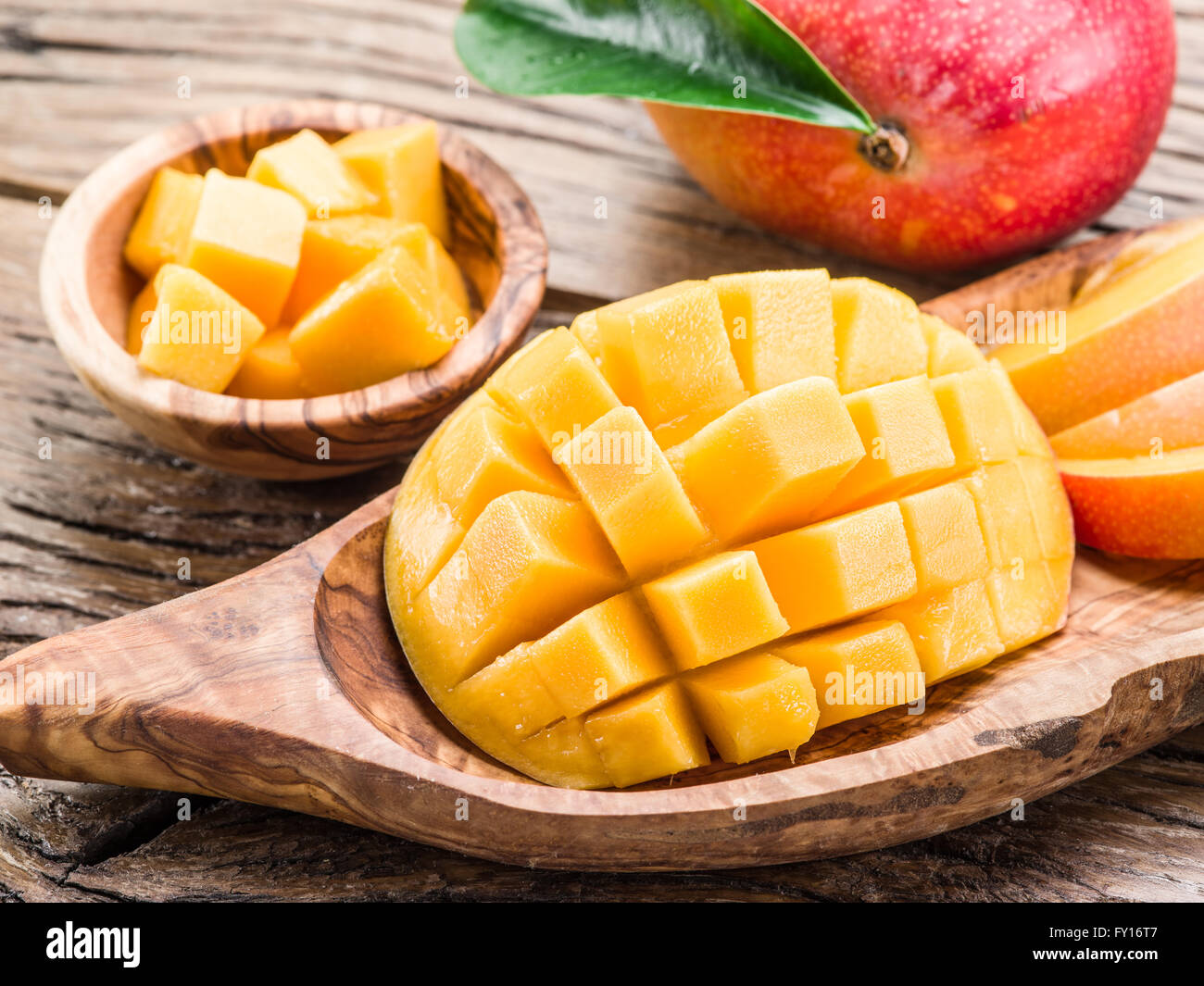 Mango fruit and mango cubes on the wooden table. - Stock Image