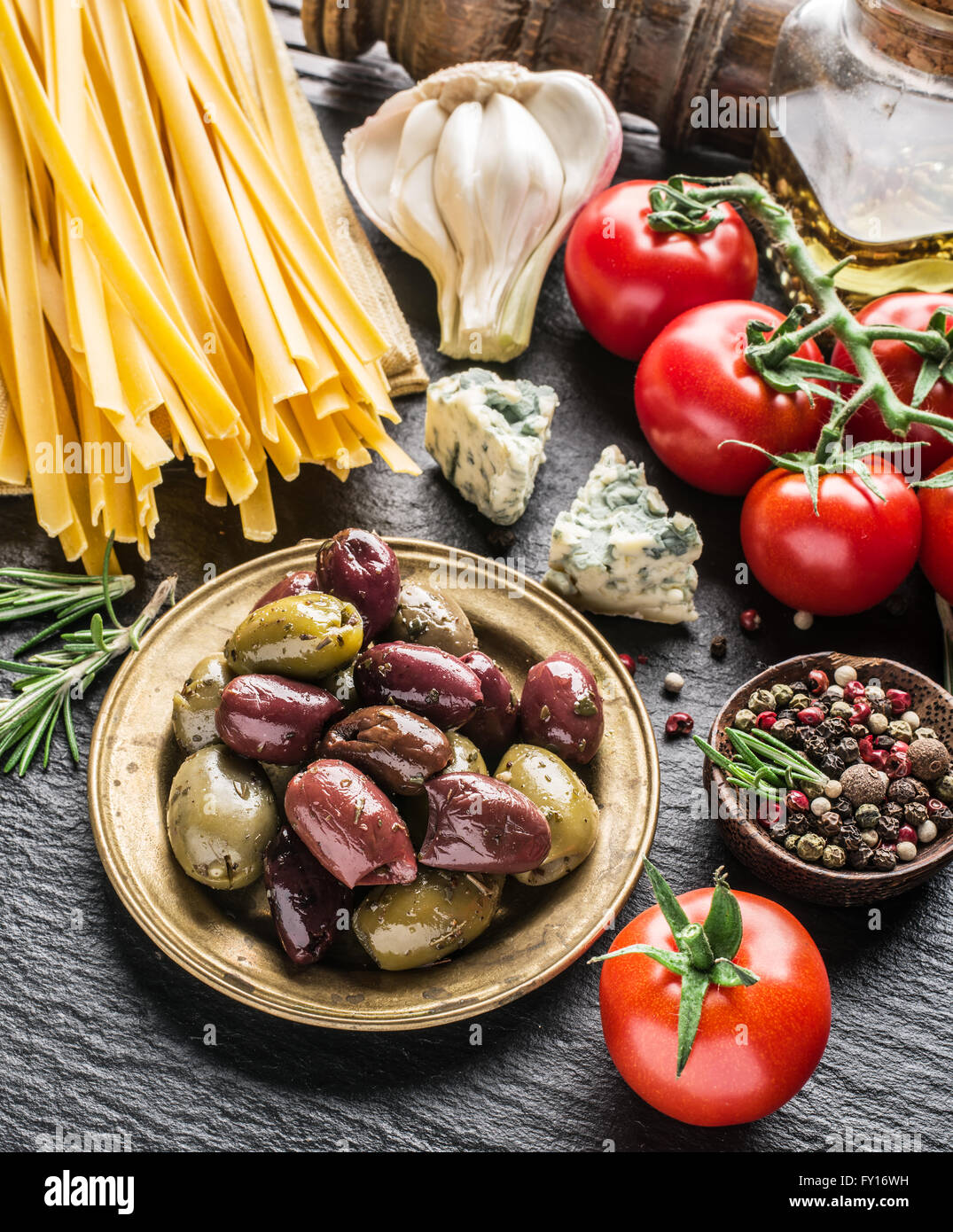Pasta ingredients. Cherry-tomatoes, spaghetti pasta, rosemary and spices on a graphite board. - Stock Image