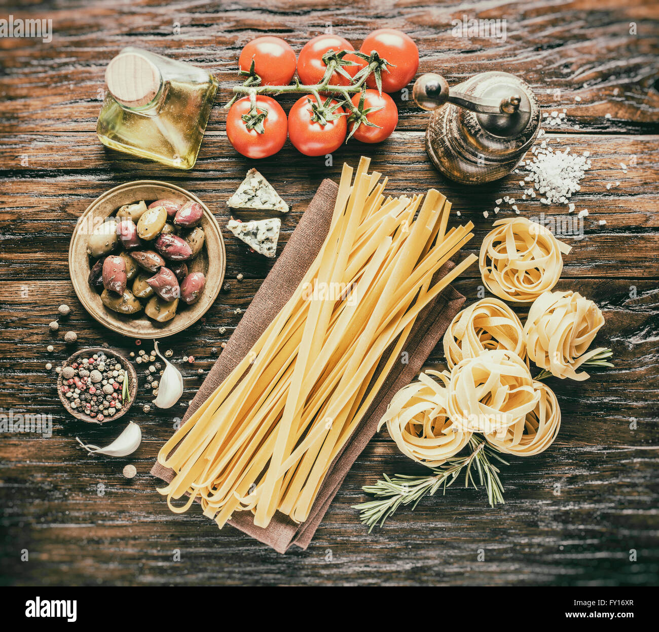 Pasta ingredients. Cherry-tomatoes, spaghetti pasta, rosemary and spices on the wooden table. Vintage style. - Stock Image