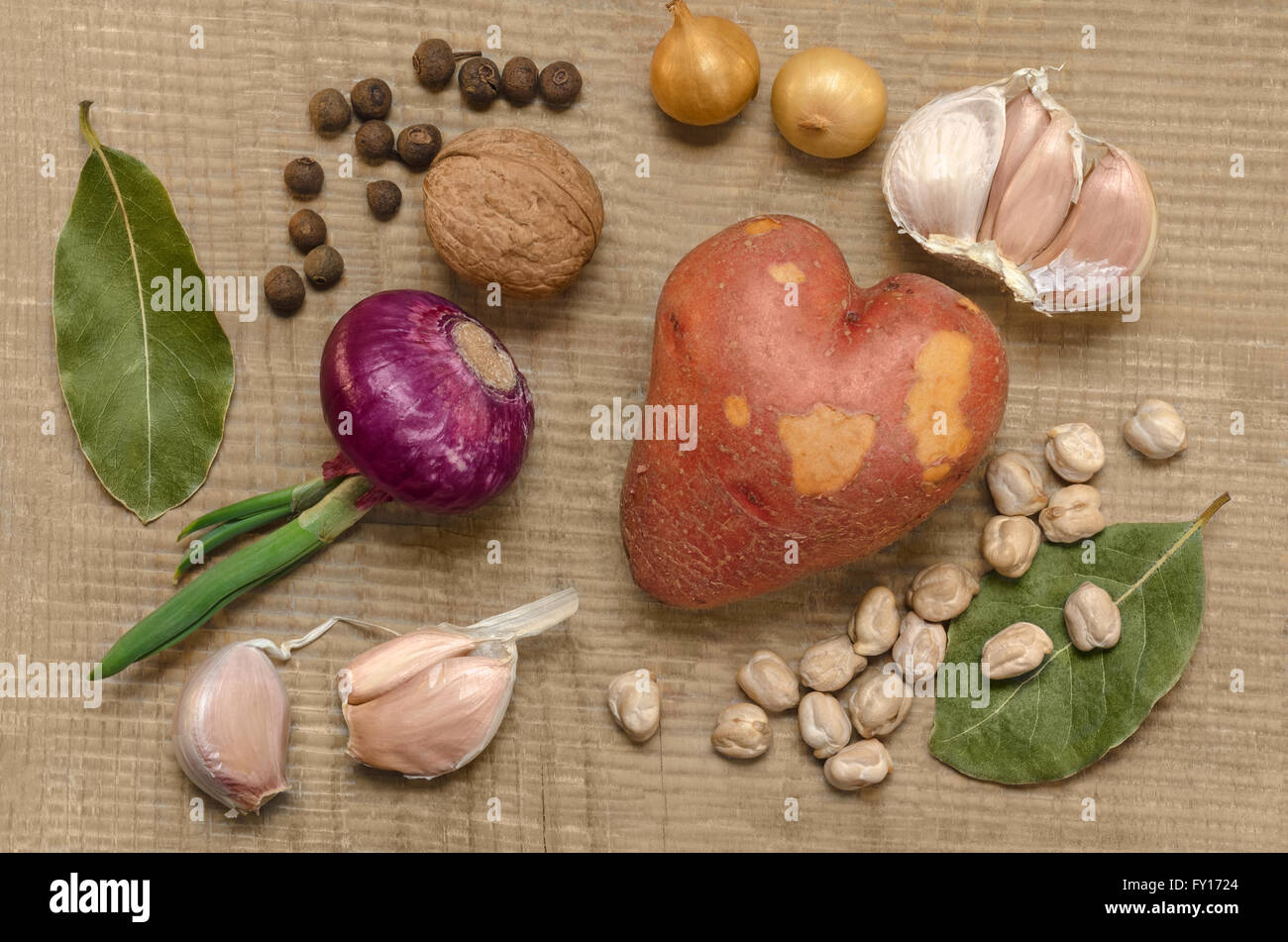 Raw potatoes and spices, on the old wooden surface. - Stock Image
