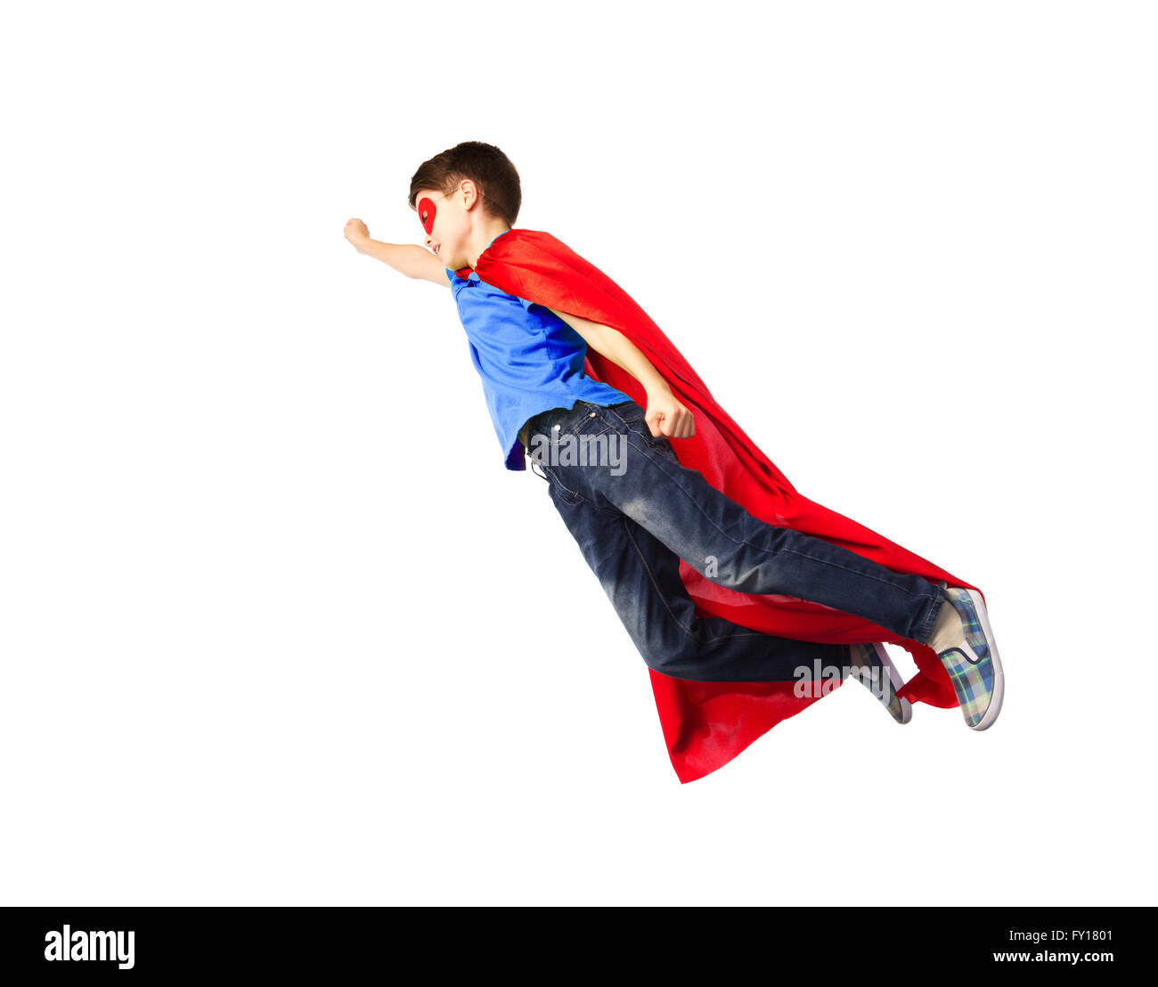 boy in red superhero cape and mask flying on air - Stock Image