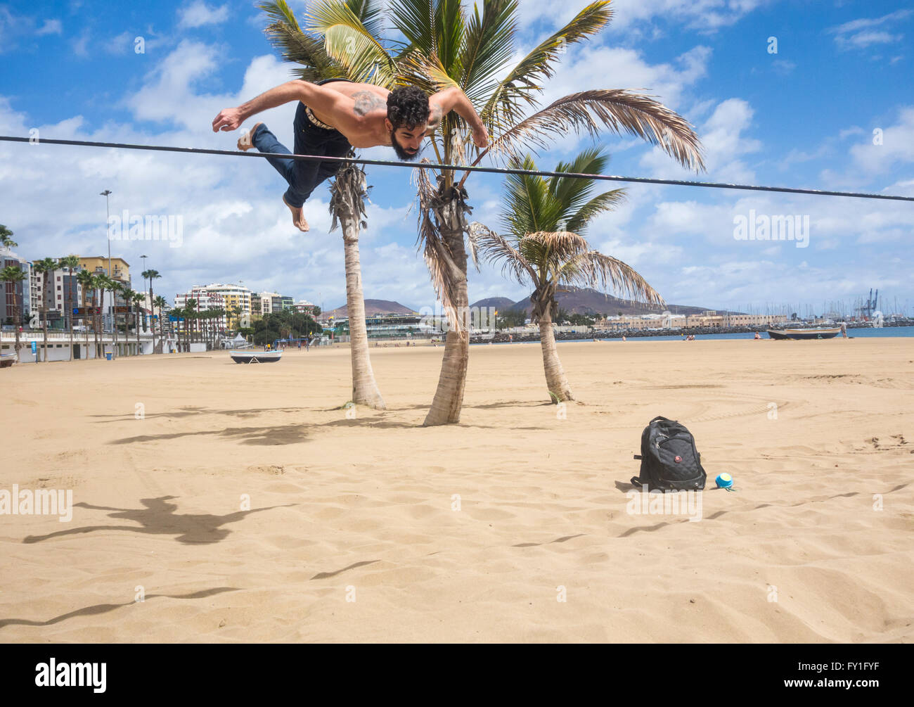 Man performing somersaults and gymnastic dismounts on slackline tied between plam trees on beach in Spain - Stock Image