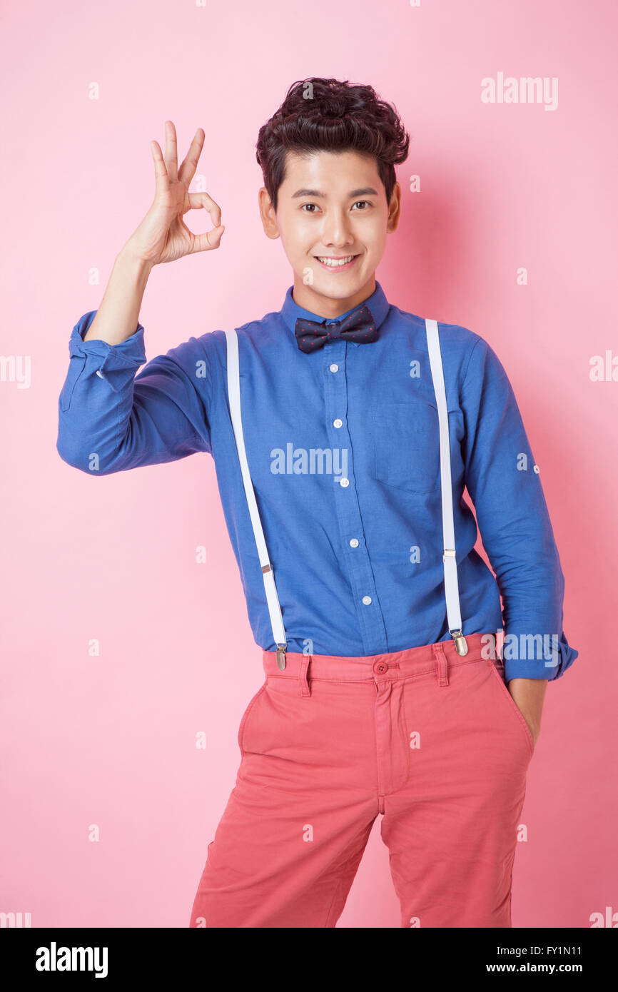 Smiling young man in his early twenties in retro style showing ok sign with one hand in pocket staring at front - Stock Image