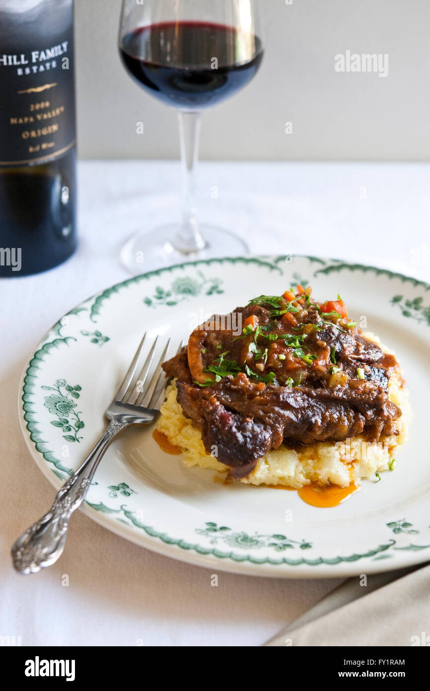 Braised Beef Shank with mashed potatoes and glass of red wine. - Stock Image