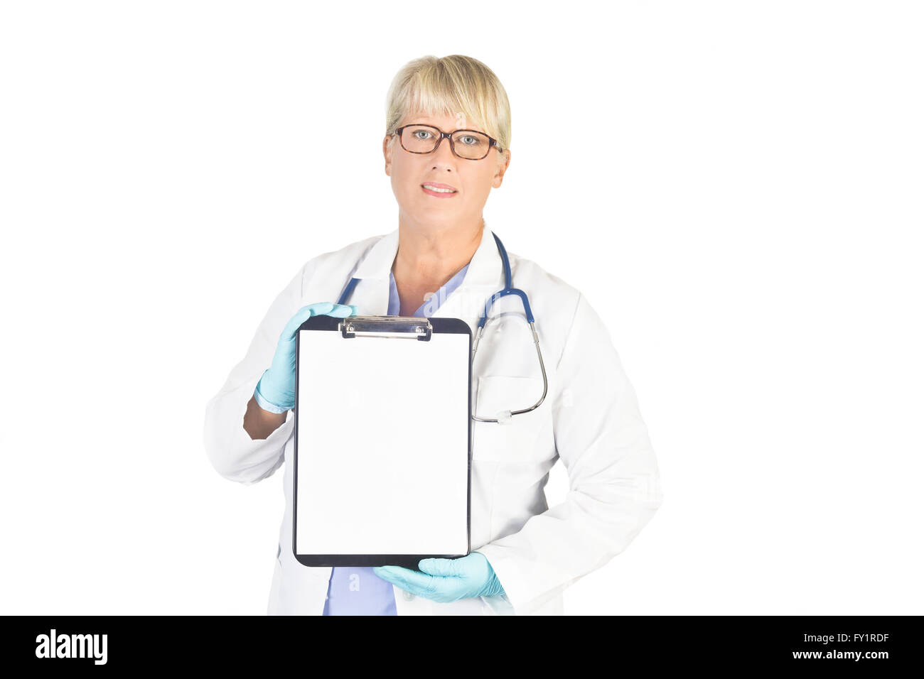 Mature nurse with blank clipboard on white. Model is an actual nurse and her recognizable photos are exclusive to - Stock Image