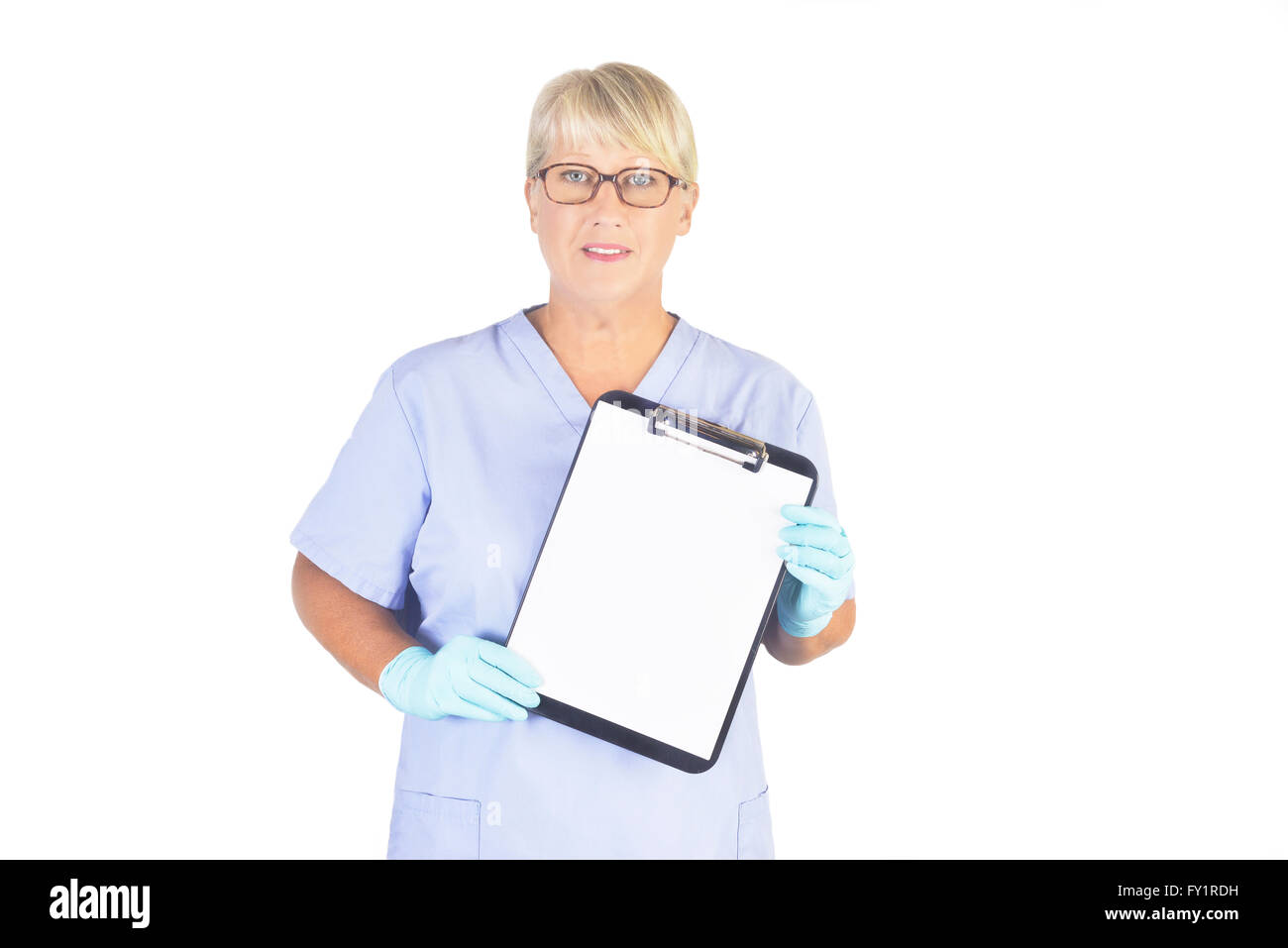 Smiling older nurse with blank clipboard on white. Model is an actual nurse and her recognizable photos are exclusive - Stock Image