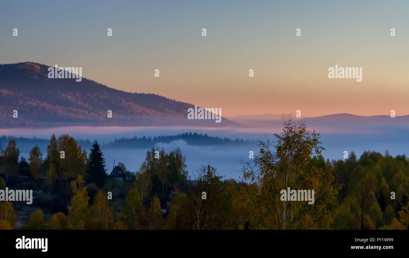 Autumn dawn over forest, fog and mountain in the background in Sheregesh, Siberia, Russia - Stock Image