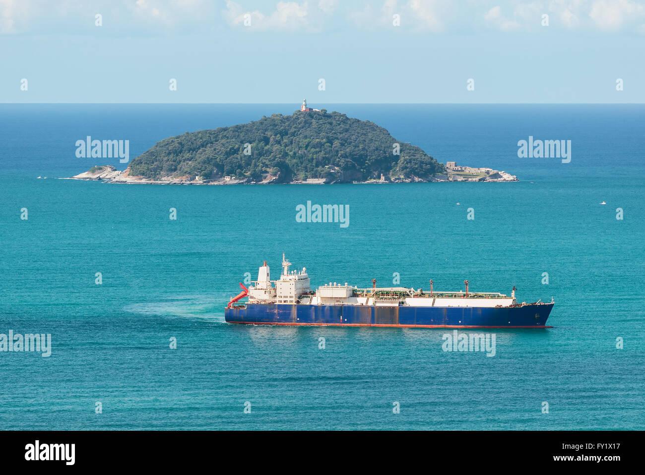 tanker ship sailing in the sea near an island - Stock Image