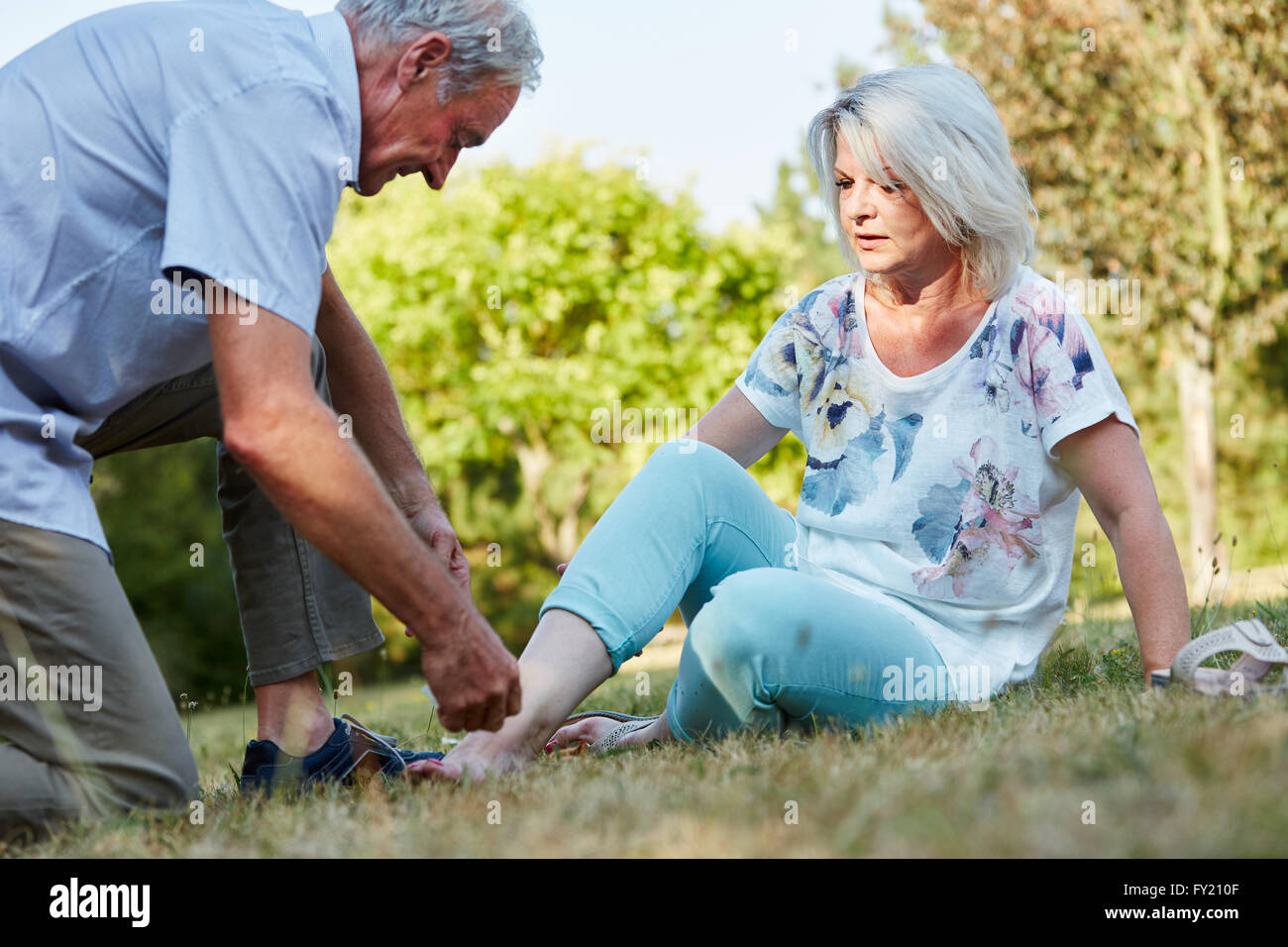 Old man helps woman with sprained ankle in the nature - Stock Image