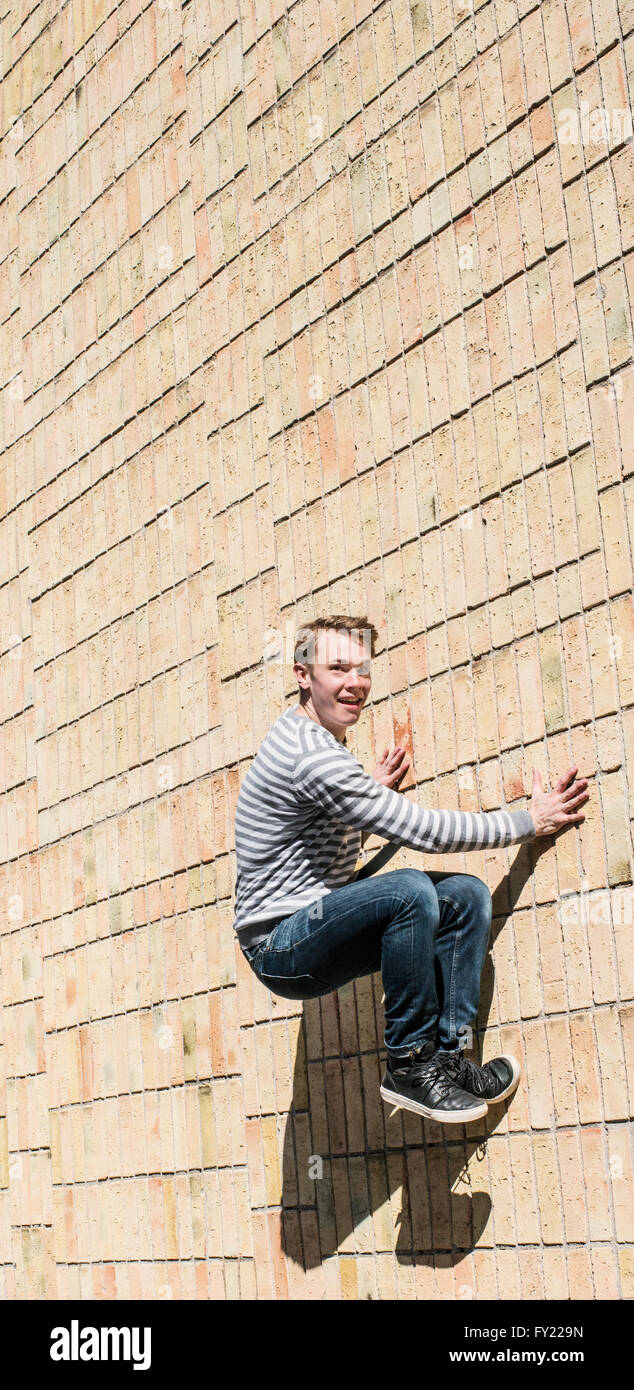 Young man doing parkour jump on brick wall, Sweden - Stock Image