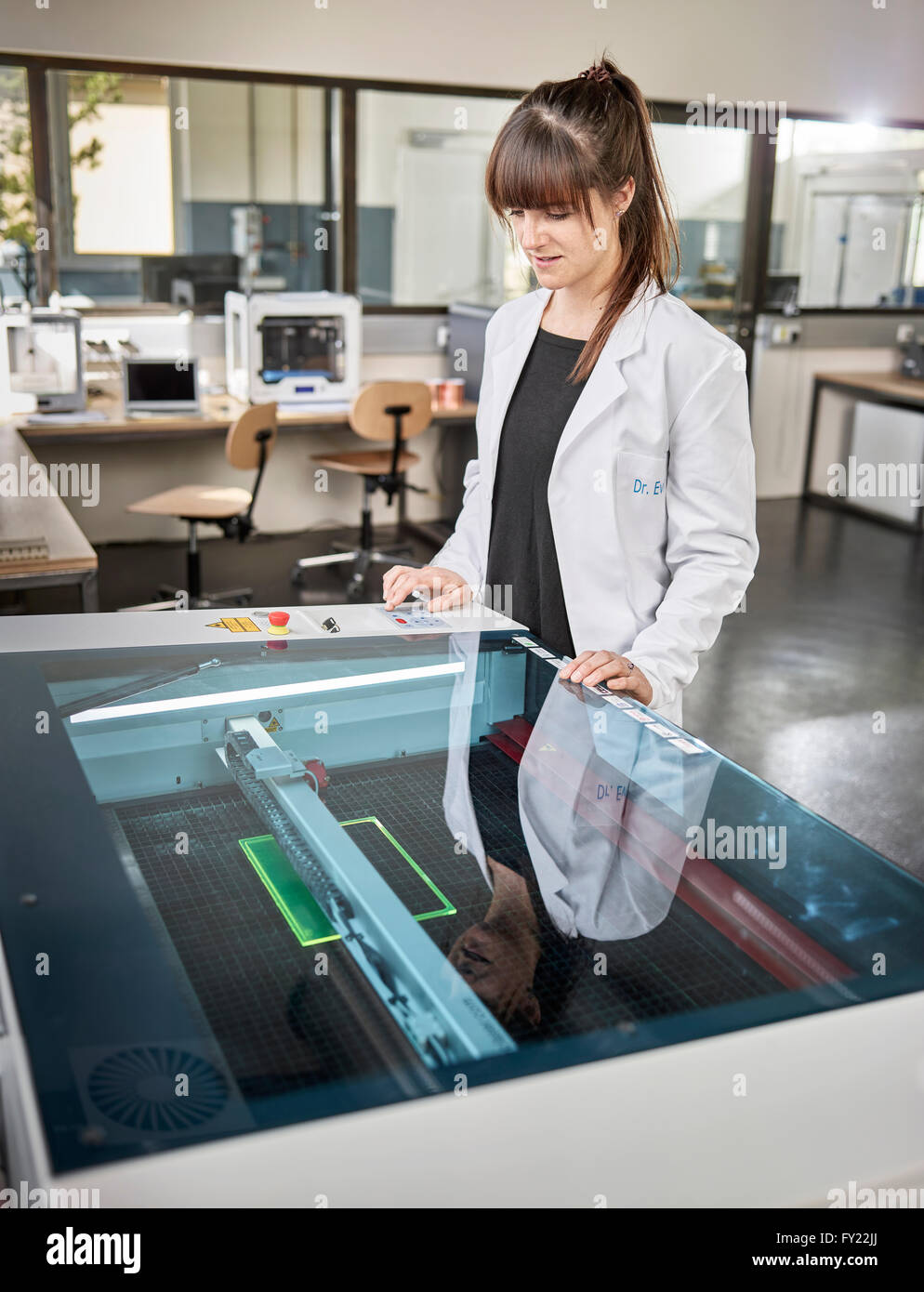 Female technician, 20-25 years, with a white lab coat, using a laser cutter in an electronics laboratory, Wattens - Stock Image