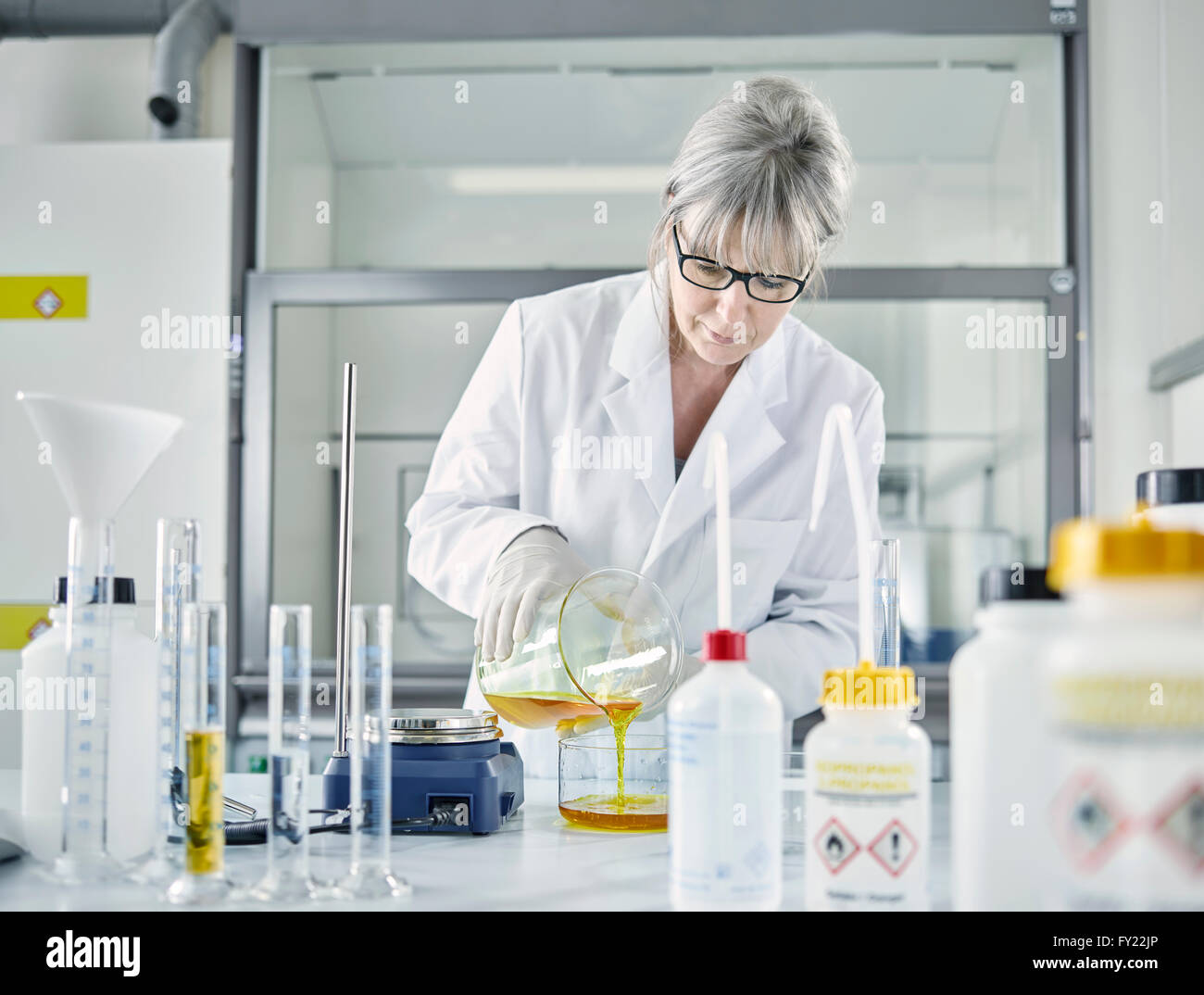 Female analytical chemist, gray hair, 50-55 years, filling a chemical mixture of water and Potassium ferrocyanide - Stock Image