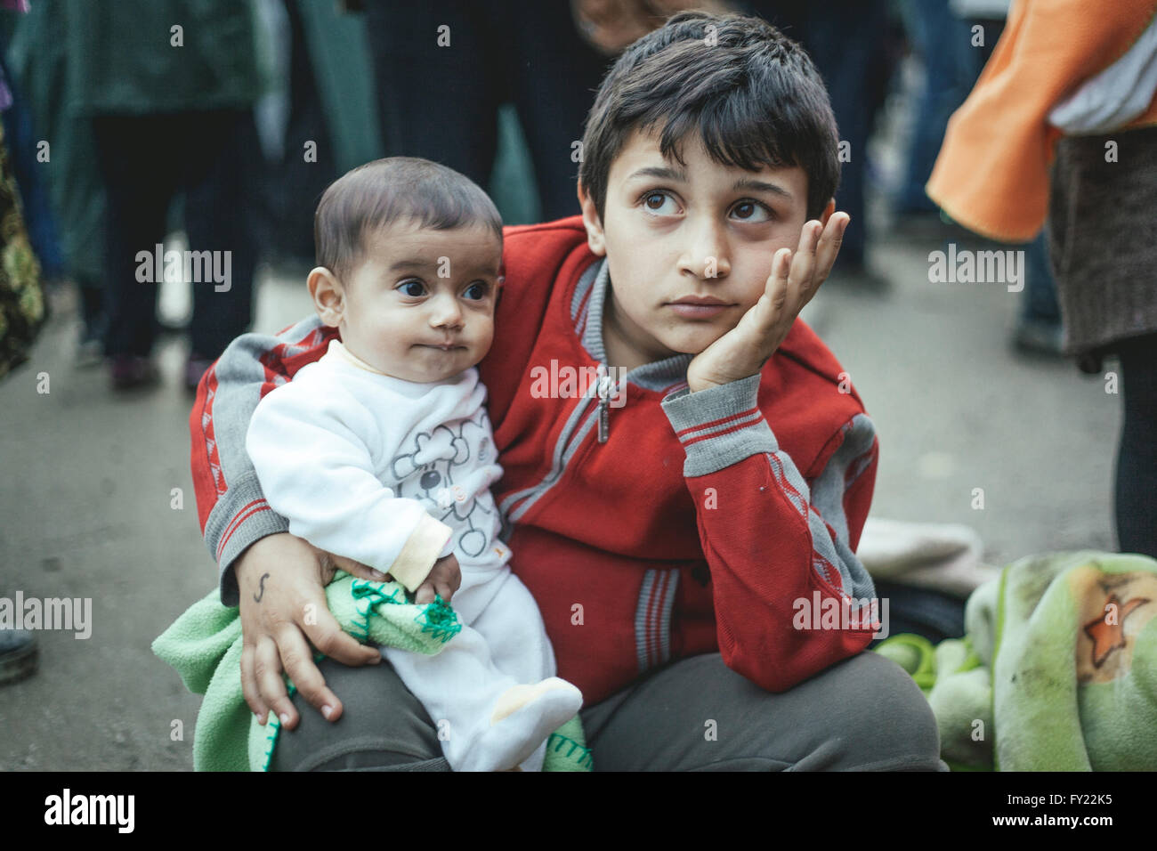 Boy from Syria after arriving with his little brother, refugee camp in Idomeni, border with Macedonia, Greece - Stock Image