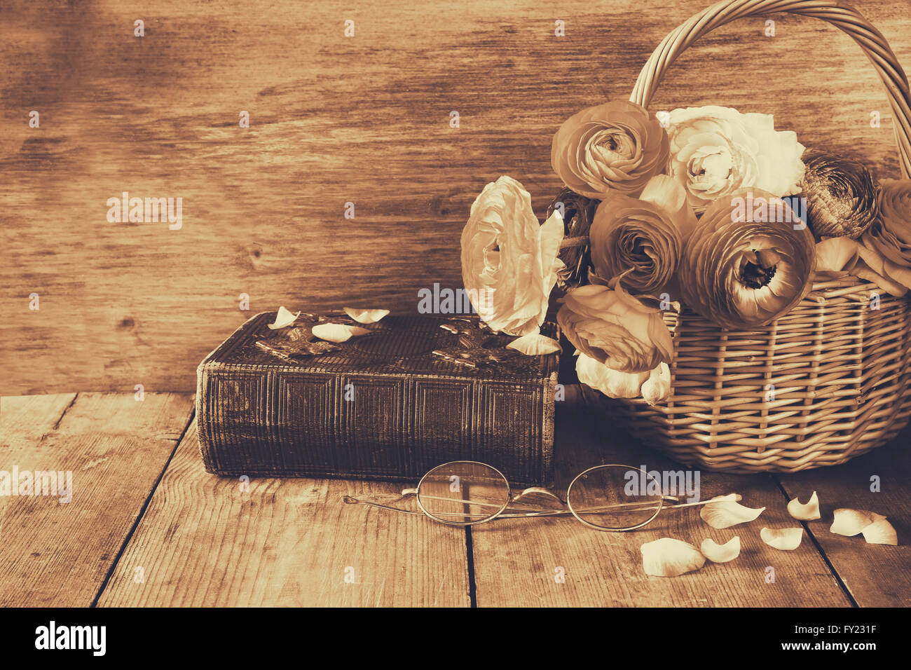 a5cfecb2eb0e2 old book and glasses next to beautiful field flowers on wooden table. vintage  filtered.