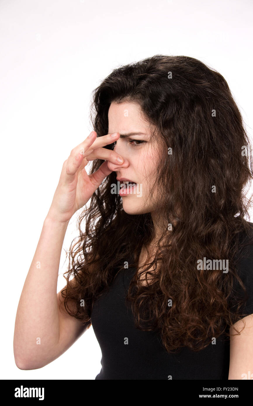 Woman pinches her nose in response to a stinky and smelly odor. - Stock Image
