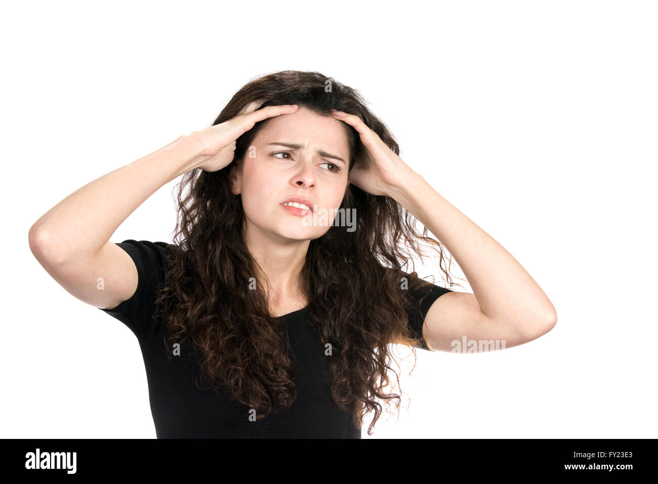 Anxious young businesswoman runs her fingers through her hair as she worries and stresses about her situation. Stock Photo