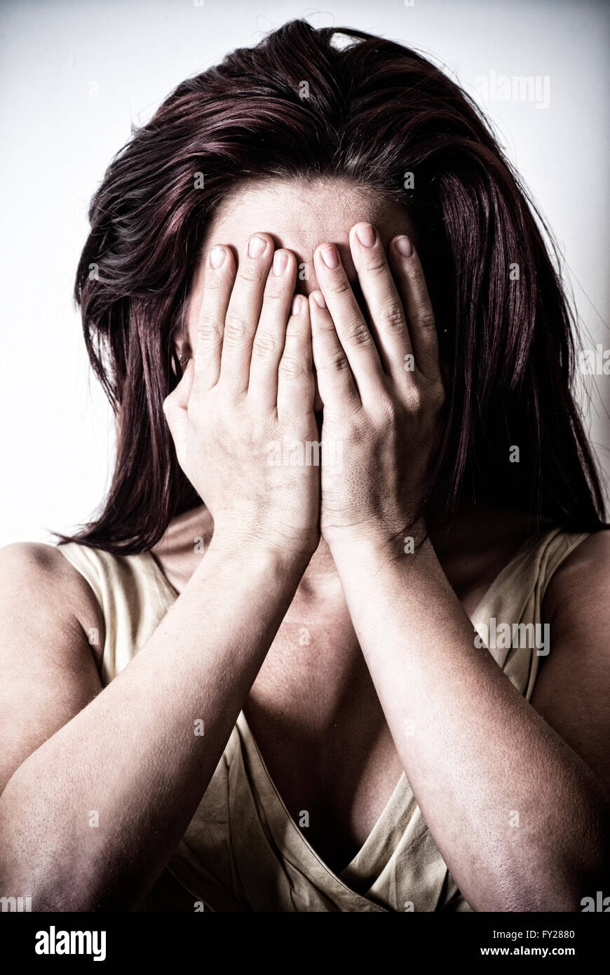 Young woman hiding face with her hands - Stock Image