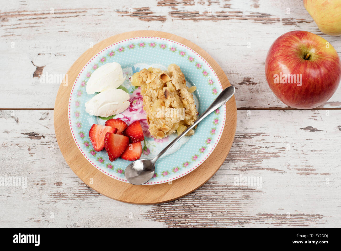 Apple crumble dessert with strawberries and vanilla cream on light rustic wooden background - Stock Image