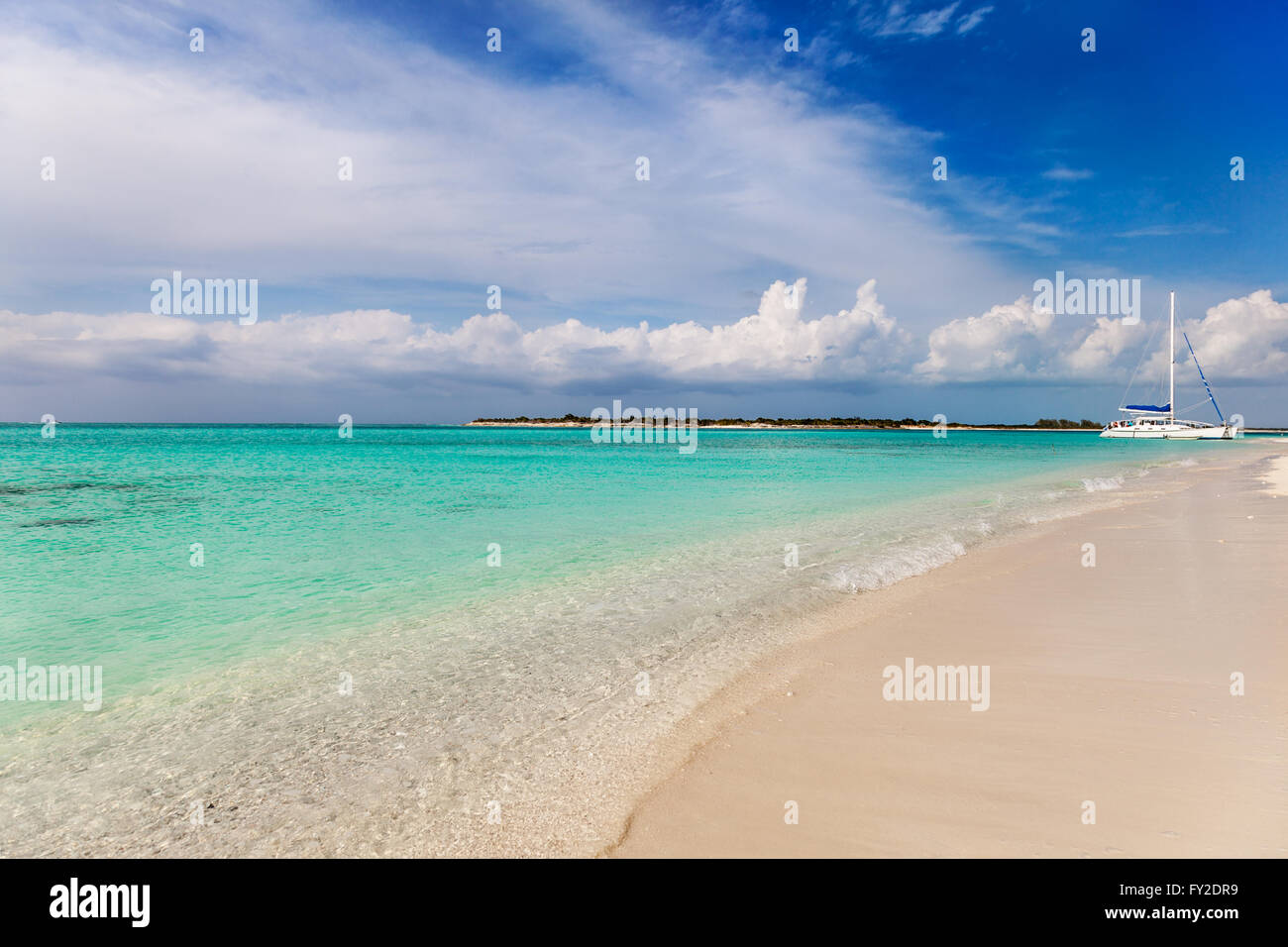 Catamaran on deserted white sand beach - Stock Image