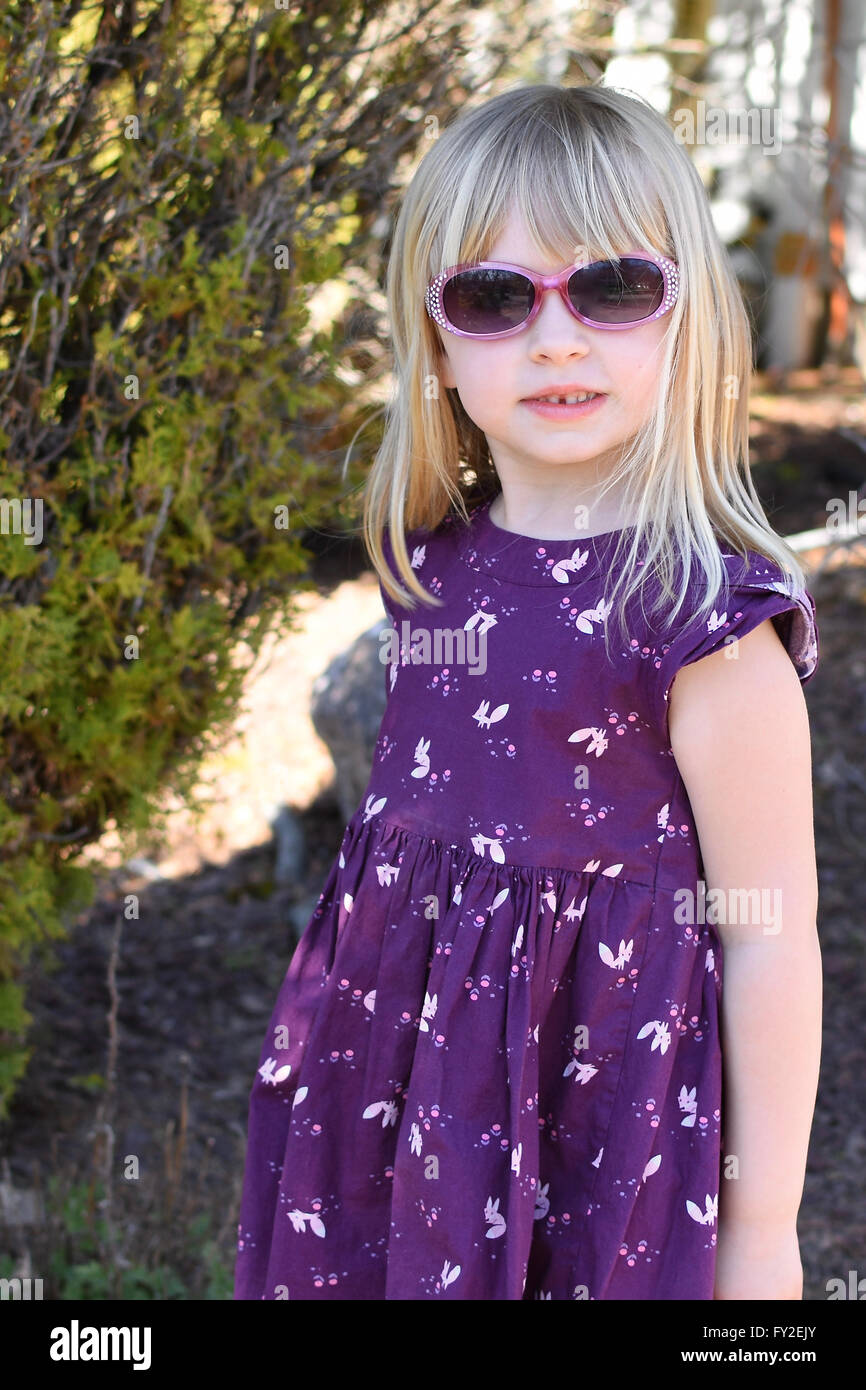 young girl modeling sunglasses in purple dress - Stock Image