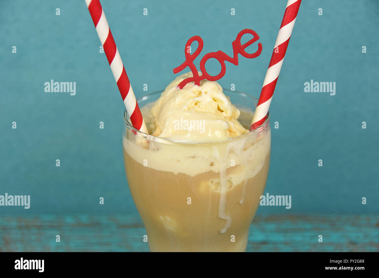 Red and white straw with love sign in root beer float on aqua painted rustic wood. - Stock Image