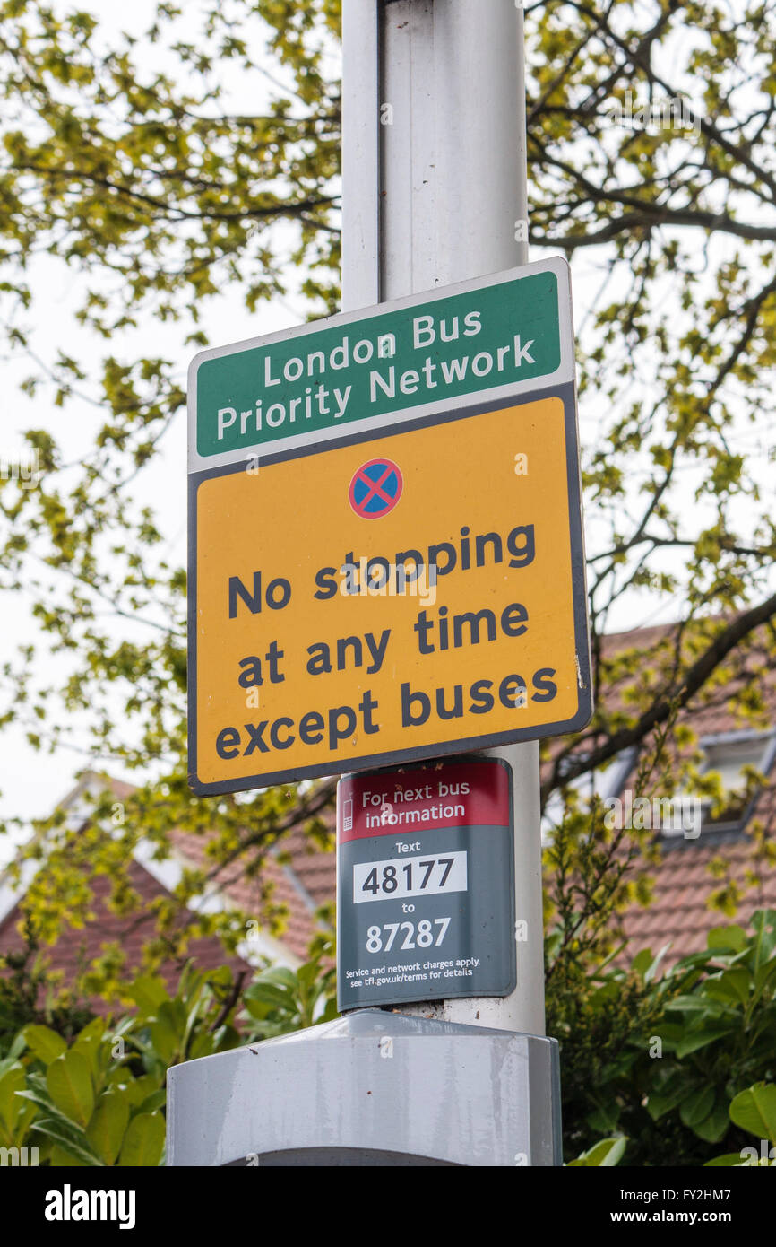 Yellow 'No stopping at any time' London Bus Priority Network sign close-up - Stock Image