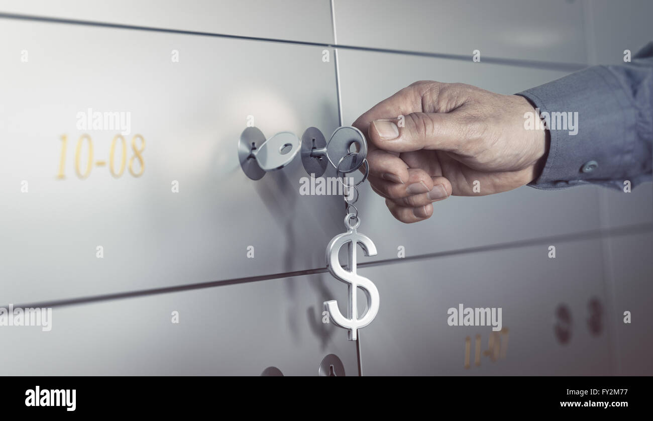 Safe deposit in a bank vault, hand about to turn a key to open a safe box. Financial concept - Stock Image