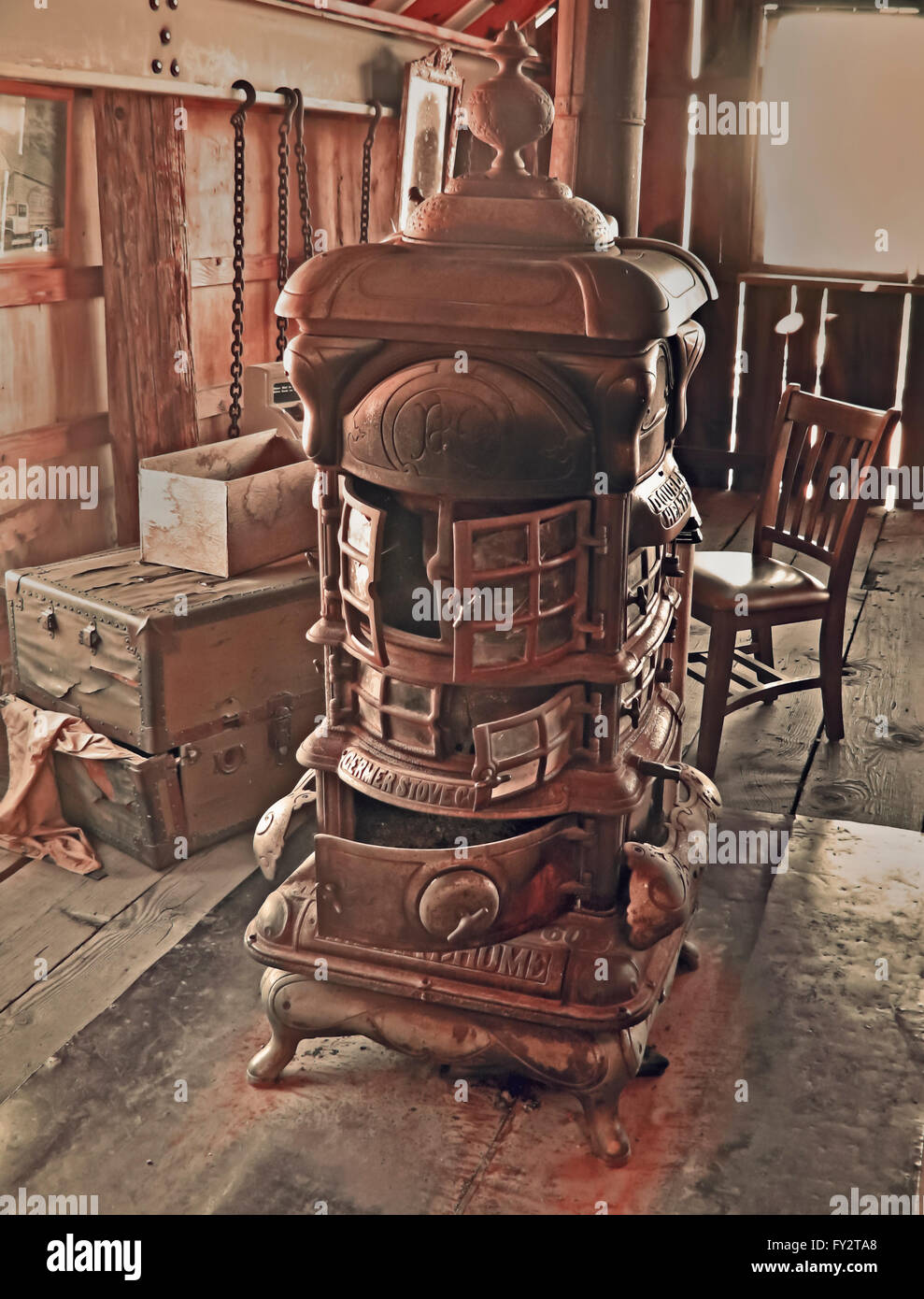 Vintage stove in abandoned barn in sepia colors  on wooden floor. - Stock Image