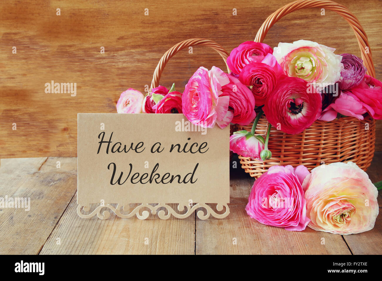 pink flowers in the basket next to card with phrase: HAVE A NICE WEEKEND, on wooden table - Stock Image