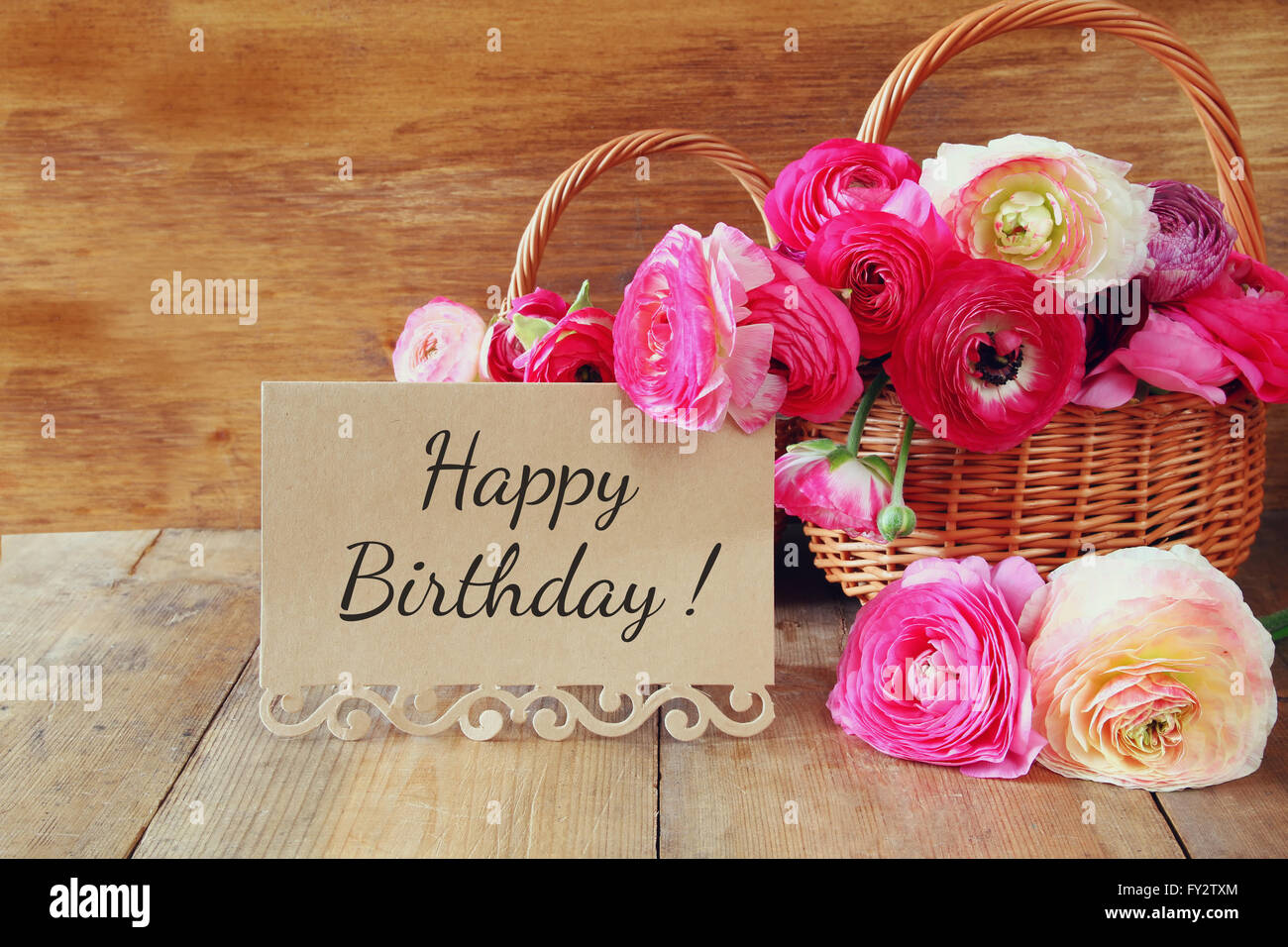 Happy birthday spring flowers stock photos happy birthday spring pink flowers in the basket next to card with phrase happy birthday on wooden izmirmasajfo
