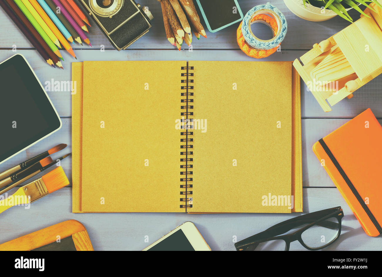 top view photo of blank notebook, old camera and school supplies on wooden table. vintage filtered - Stock Image