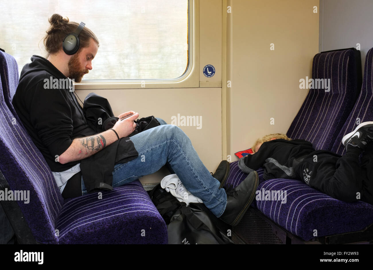 Male and child passengers travelling on a train with male setting a bad example by putting his feet on seats in - Stock Image
