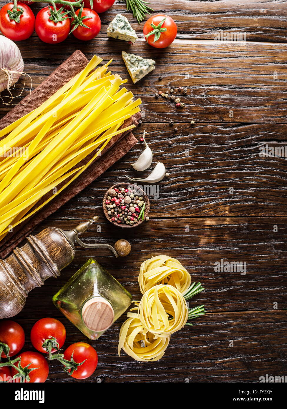 Pasta ingredients. Cherry-tomatoes, spaghetti pasta, rosemary and spices on the wooden table. - Stock Image