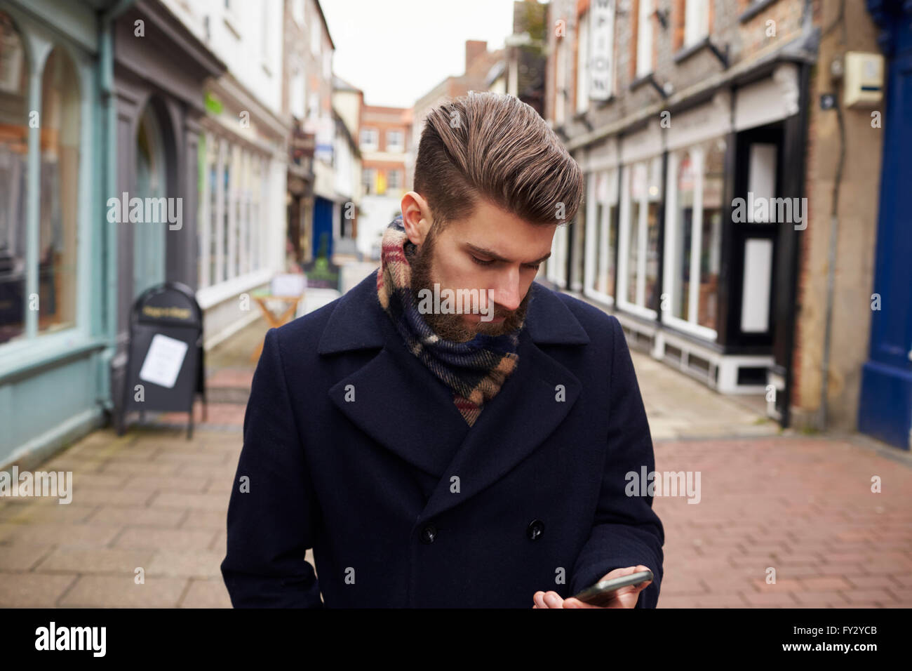 Man Walking Down Urban Street Checking Text Message On Phone - Stock Image