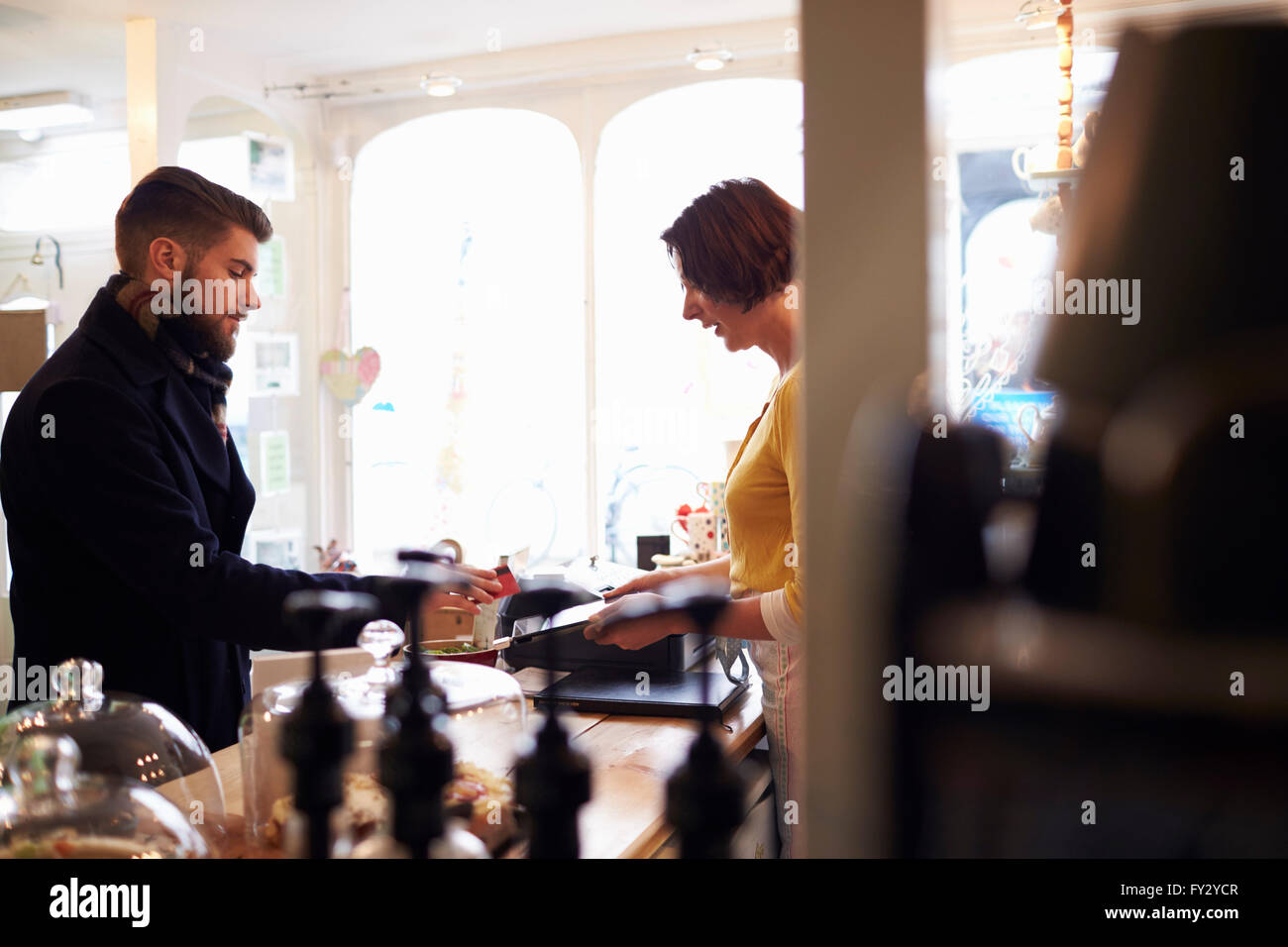 Customer In Cafe Paying Using Reader On Digital Tablet - Stock Image